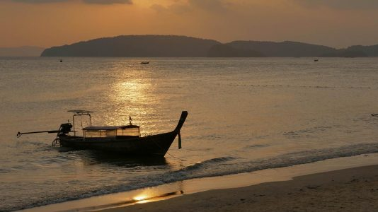 Silhouetted Long Tail Boat on Ao Nang Beach at Sunset in Thailand