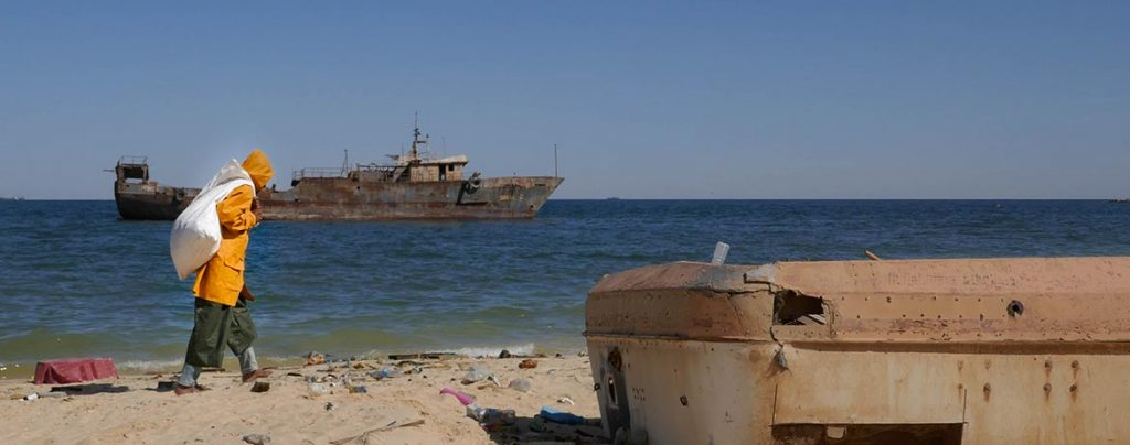 Man in Yellow Fisherman's Coat Walks Past Shipwreck in Nouadhibou - Mauritania
