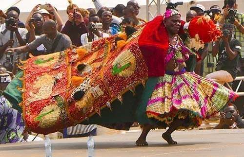 Cultural adventure is still adventure. Vodun dancer in red cape at festival in Ouidah, Benin.