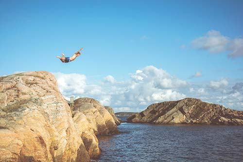 Cliff diver mid-leap