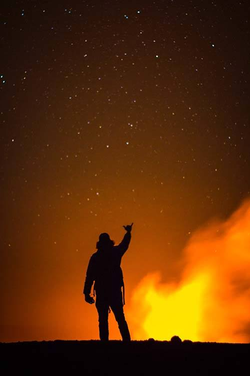 Silhouetted guy standing at fiery edge of volcano