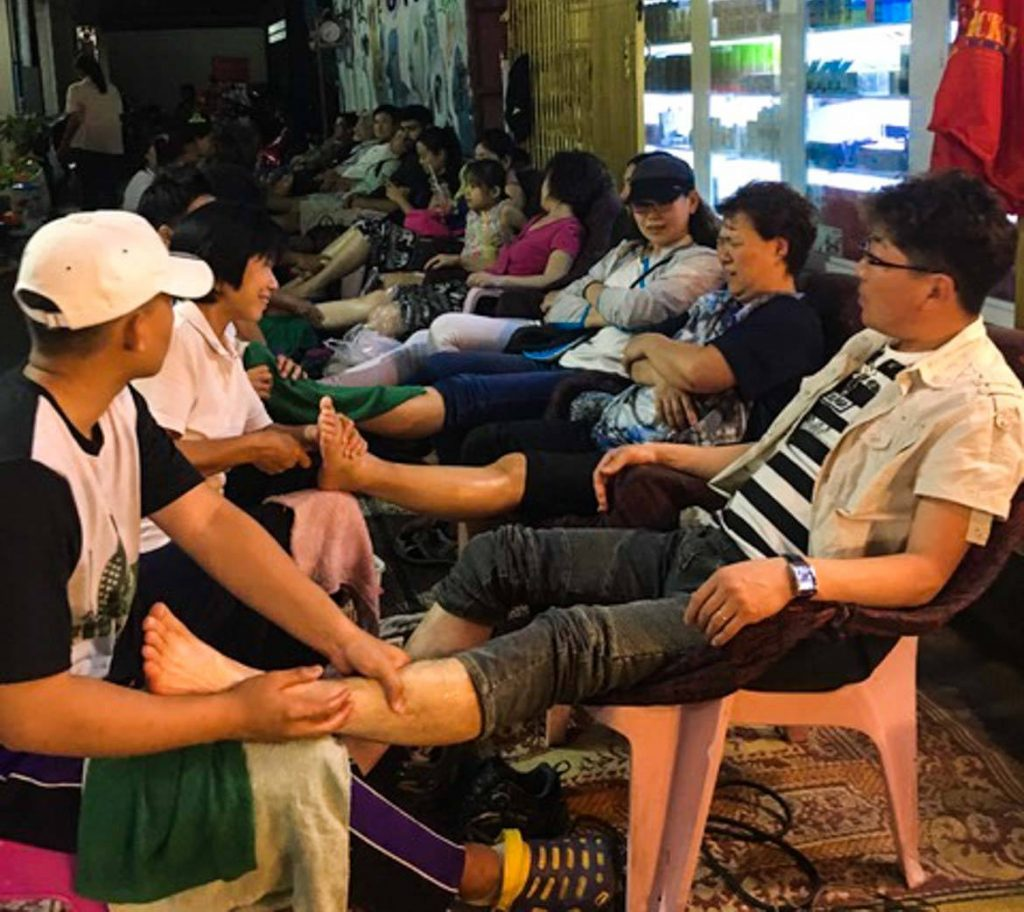 People getting foot massages at the Chiang Mai Sunday Night Market in Thailand