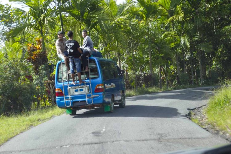 Guys Hanging Off of Van Going Around Curve in Road in Paradise Setting of Flores Island